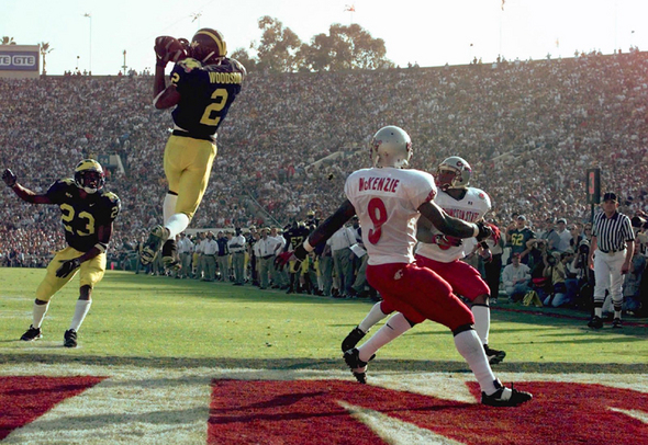 eMichigan's cornerback Charles Woodson (2) leaps to make an interception in the end zone in the first half on a pass from Washington State's Ryan Leaf during the 84th Rose Bowl in Pasadena, Calif., Thursday, Jan. 1, 1998. Watching the play are Michigan's William Peterson (23) and Washington States Kevin McKenzie (9). Player at right unidentified.(AP Photo/Mark J. Terrill)